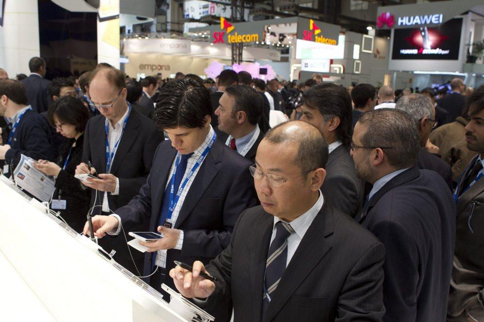 Un grupo de asistentes prueba los nuevos teléfonos expuestos en el...