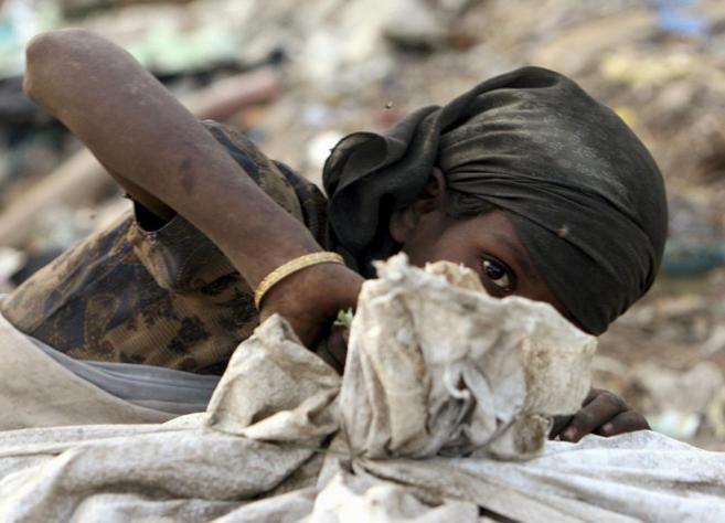 Una niña carga con un saco de basura en un vertedero de Nueva Delhi.