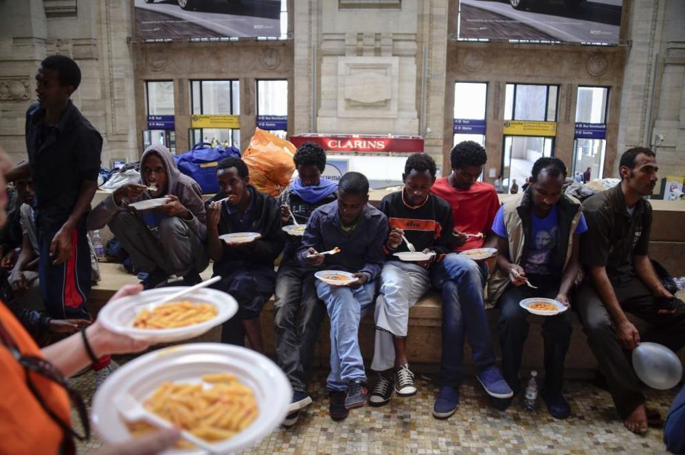 Migrantes de Eritrea reciben comida en la estación de ferrocarril de...