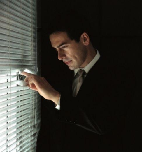 Un hombre espía a través de una ventana