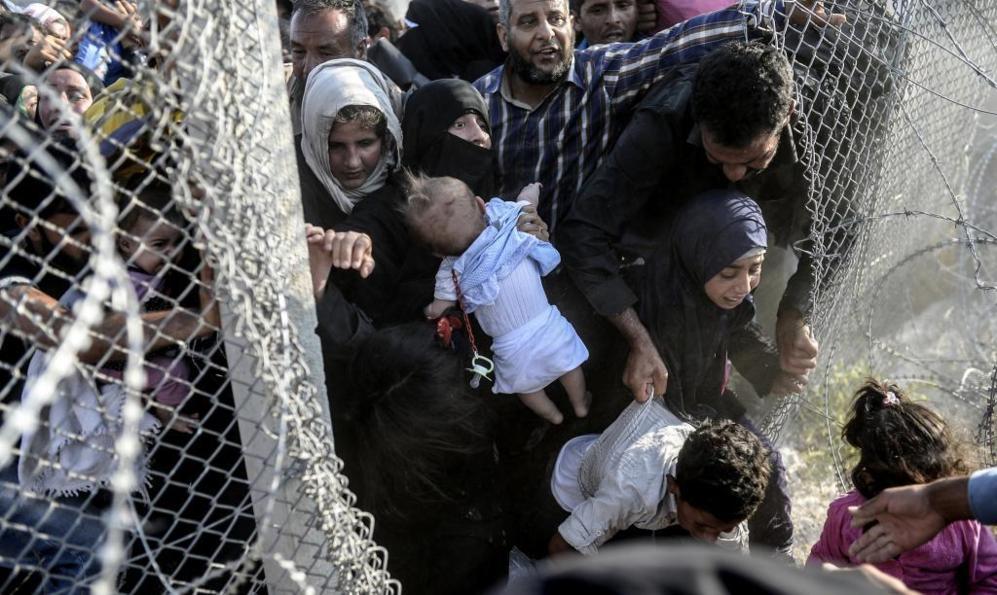 Refugiados sirios atraviesan el alambre de espino que separa la ciudad...