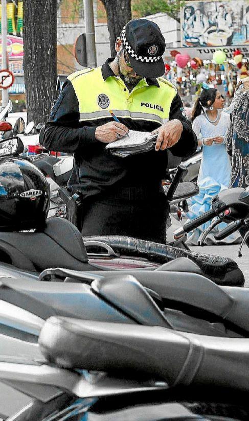 Un agente pone multa las motos aparcadas en la Feria.