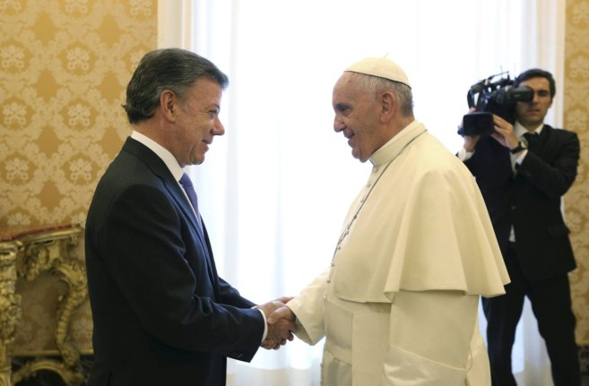 El presidente colombiano, Juan Manuel Santos, estrecha la mano al Papa...
