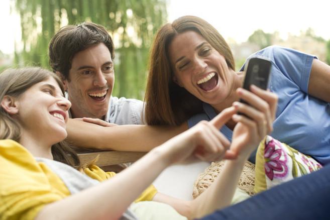 tres personas se ríen viendo un vídeo en un teléfono móvil