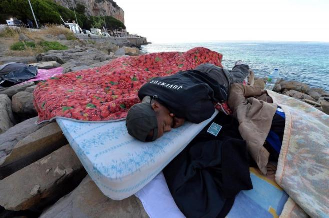 Un inmigrante duerme sobre las rocas en la localidad italiana de...