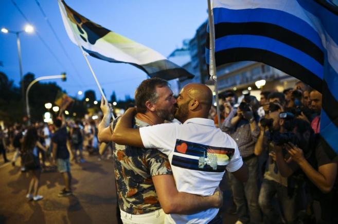 Dos hombres se besan durante la marcha del orgullo gay en Atenas,...
