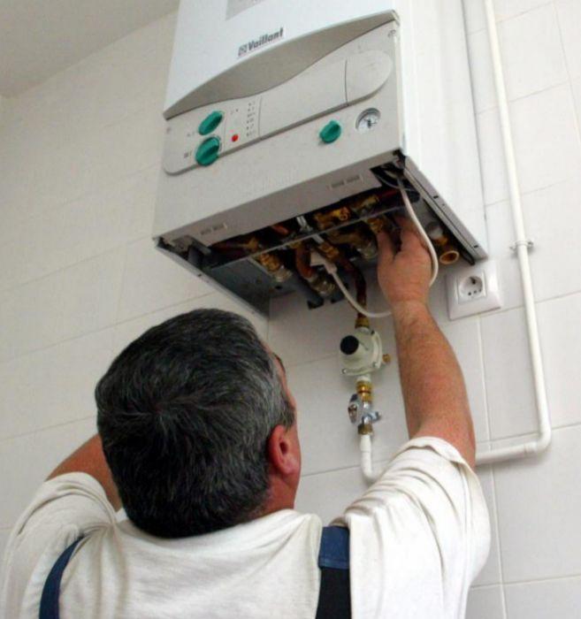 Un operario arregla una caldera de gas.