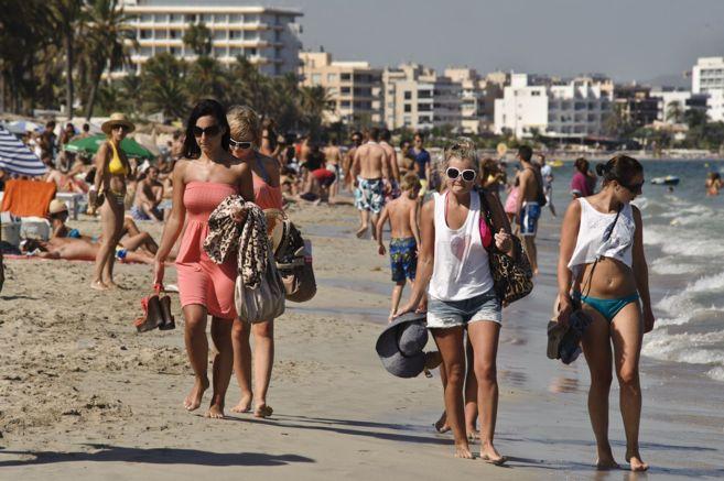 Turistas paseando por la orilla de Platja d'en Bossa.