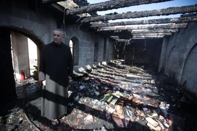 Un cura inspecciona los daños de la parte afectada por el incendio de...