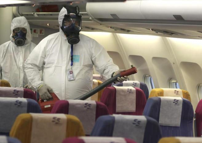 Un operario rocía con desinfectante un avión de Thai Airways