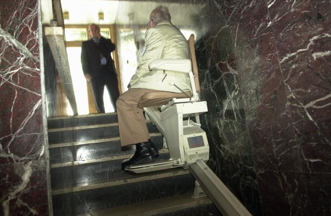 Una persona de edad avanzada sube las escaleras de un portal con la...
