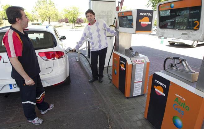 Cliente y gasolinero en una estación de servicio Repsol.