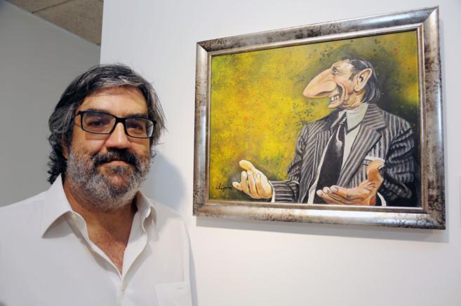 El dibujante Ángel Idígoras, en su exposición junto a su retrato...