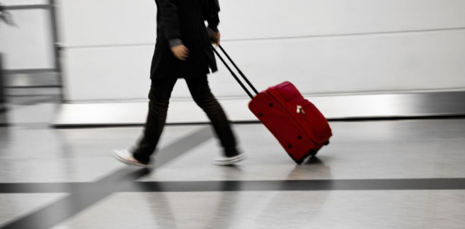 Una mujer camina con una maleta por el aeropuerto de Madrid.