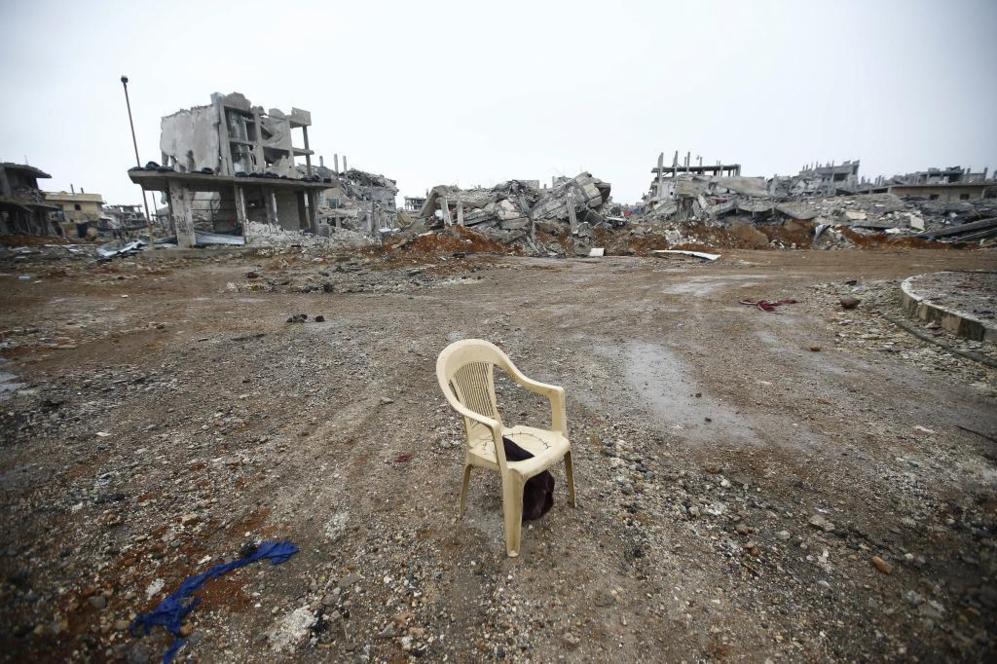 Una silla de plástico se yergue en medio de edificios destruidos en...