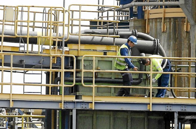 Dos operarios de Mina Las Cruces trabajan en las instalaciones...
