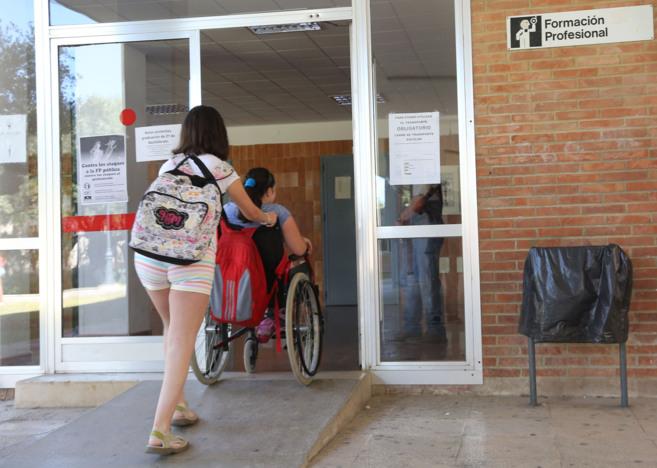 Una alumna con necesidades especiales entra en el centro, ayudada por...