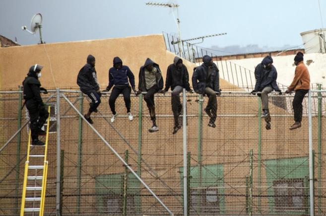 Inmigrantes encaramados en la valla de Melilla el pasado febrero.