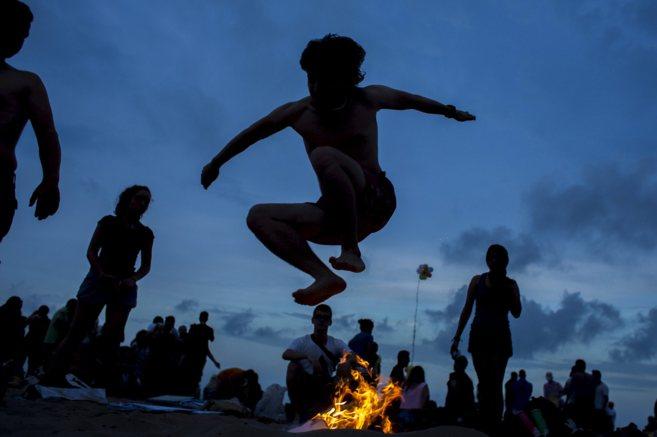 Un joven salta una hoguera durante la noche de San Juan en Valencia.