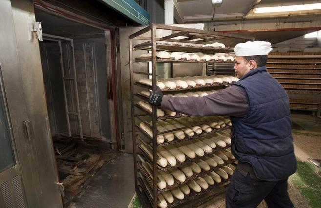 Un trabajador introduce en el horno un carro con barras de pan en una...