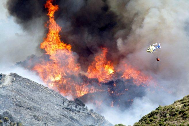 Un helicóptero durante las labores de extinción de un incendio...