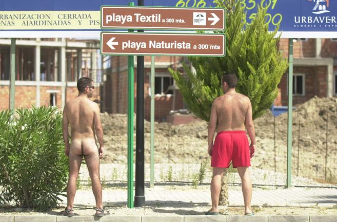 Dos bañistas junto a señalizaciones de las playas de Vera, en...