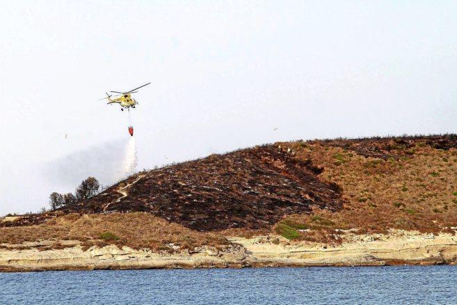 Un helicóptero realizando las últimas maniobras para sofocar el...