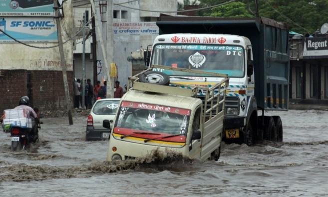 Indios intentan cruzar una calle inundada en la ciudad de Jalandhar.