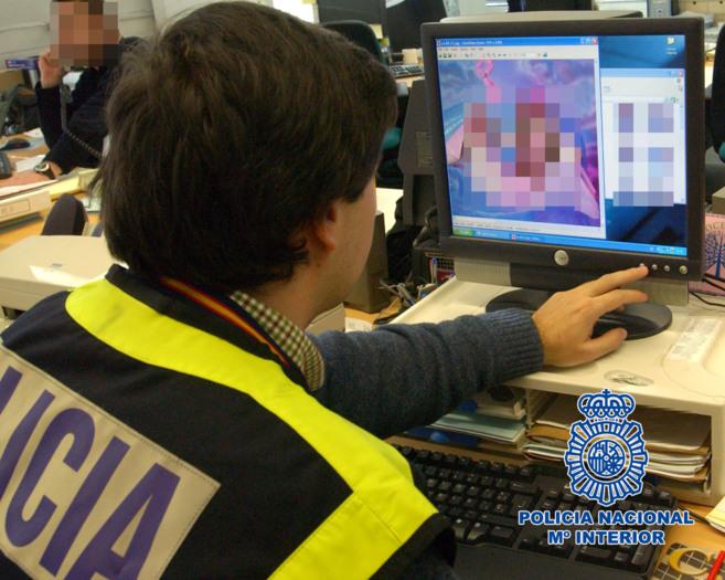 Un agente de la policía revisa el material en un ordenador.