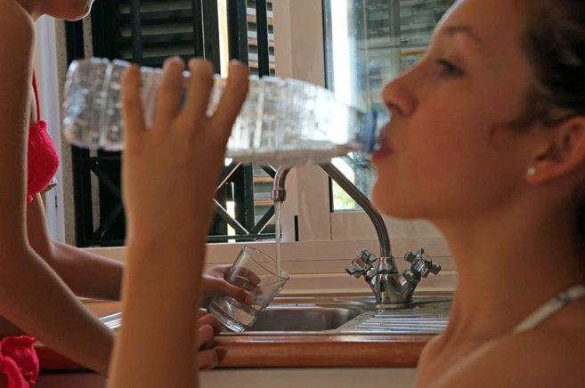 Una joven bebe agua directamente de una botella de plástico.