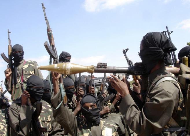 Militantes de Al Shabab enseñan sus armas en las afueras de la ciudad...