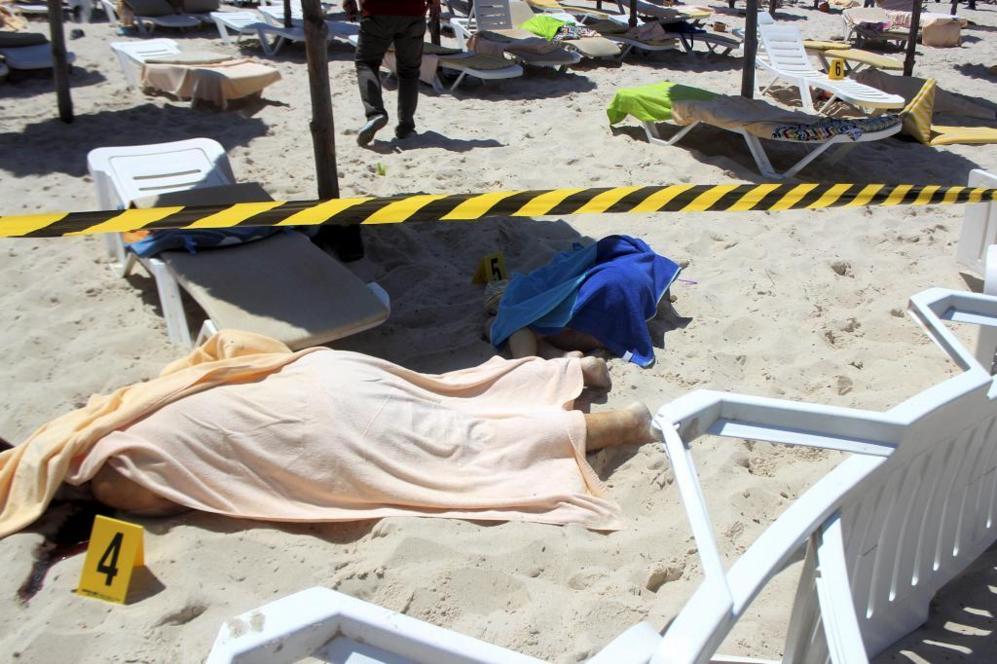 Los cuerpos de los turistas muertos durante el tiroteo yacen en la...