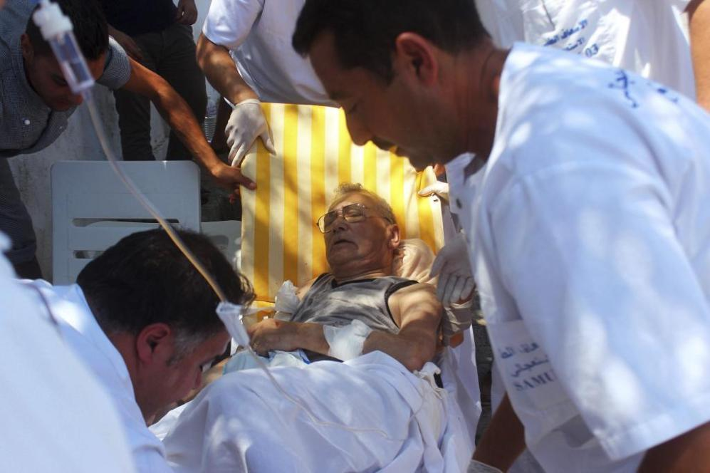 Dos sanitarios tratan a uno de los seis heridos por el ataque...