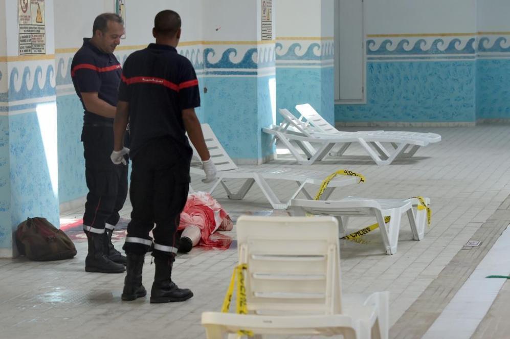 Médicos tunecinos permanecen al lado de un fallecido en la piscina...