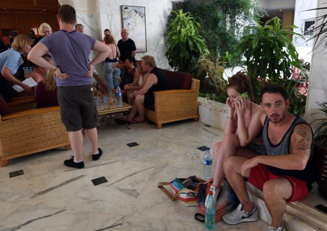 Un grupo de turistas esperan en el vestíbulo de su hotel a ser...