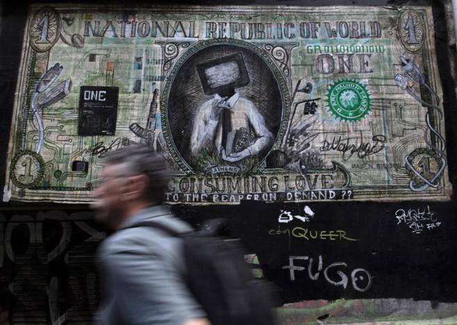 Un hombre pasea por Atenas por delante de un grafiti en contra del...