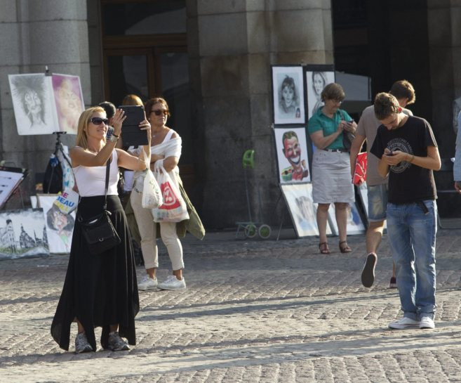 Turistas con distintos dispositivos móviles en la Plaza de Oriente de...