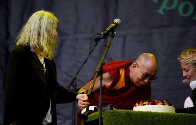 El Dalai Lama sopla las velas en compañía de Patti Smith, a la...