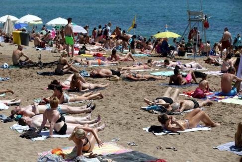 Gente tomando el sol en la playa de la Barceloneta.