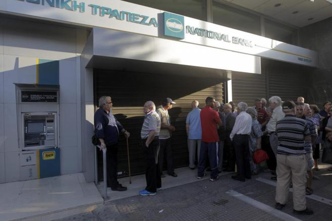 Ciudadanos griegos hacen cola ante una oficina bancaria