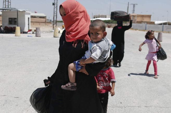 Refugiados sirios se dirigen a la ciudad de Tel Abiad (Siria) huyendo...