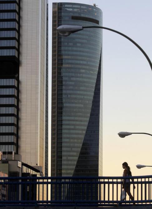 Una persona pasa junto al edificio Torre Espacio.