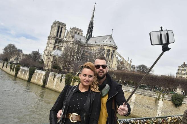 Una pareja se saca una foto con el palo 'selfie' en Paris.