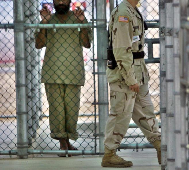 Un soldado estadounidense pasa junto a la reja de uno de los detenidos...