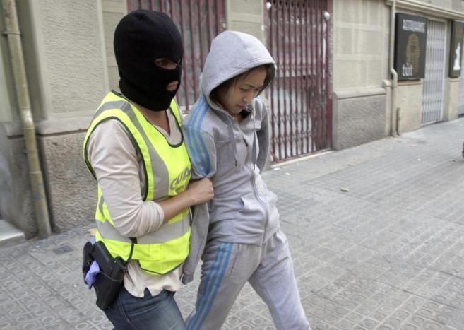 Una agente de la Guardia Civil custodia a una de las detenidas este...