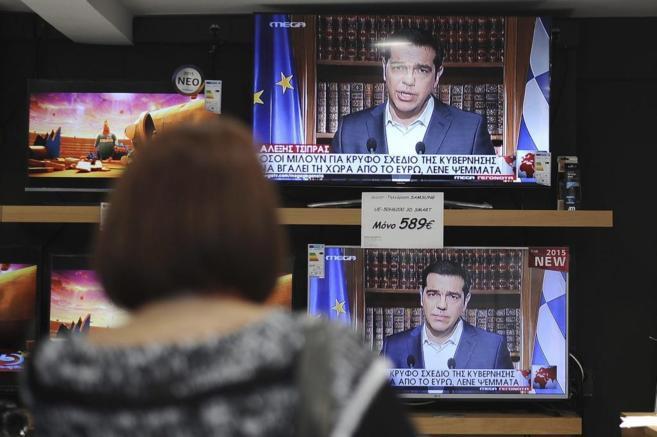 Una mujer ve el discurso televisado de Tsipras