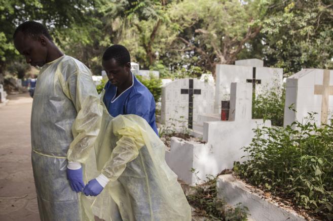Personal de enterramientos seguros se quitan el equipo de protección...