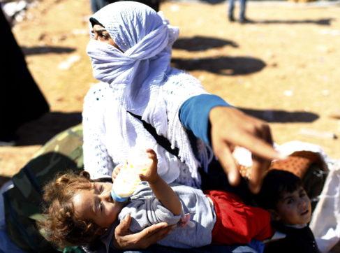 Una madre siria con sus hijos en un campo de refugiados en la frontera...