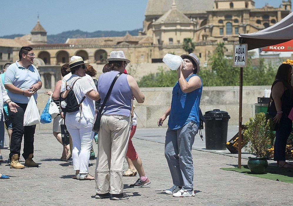 Turistas bebiendo agua en el Puente Romano de Córdoba, una de las...