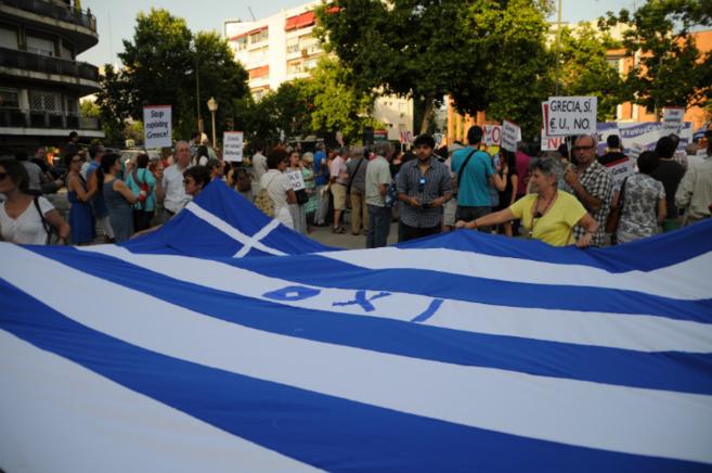 Varios manifestantes portan una bandera con el lema 'oxi' -...